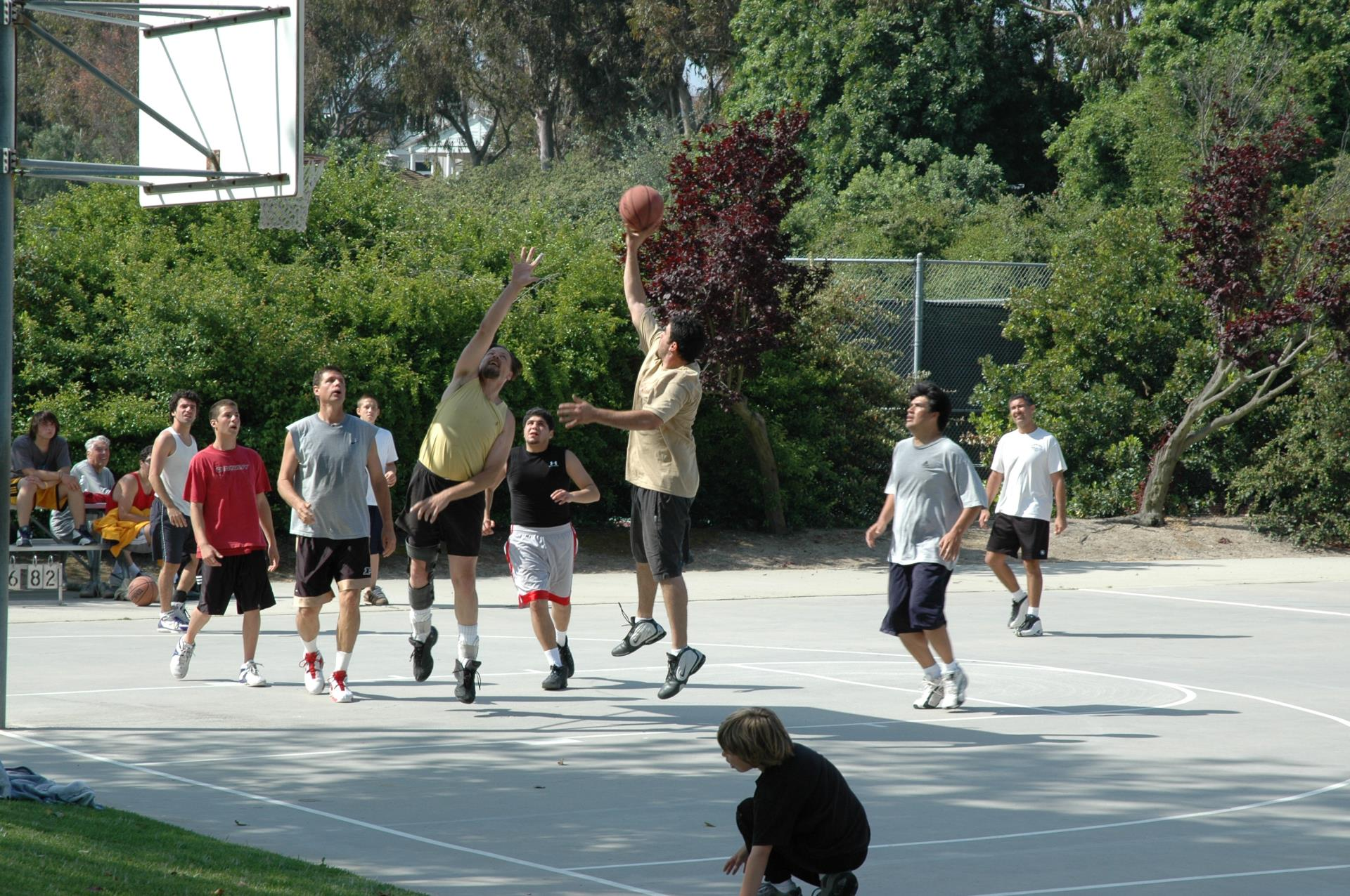 A group is playing basketball at Ernie Howlett Park